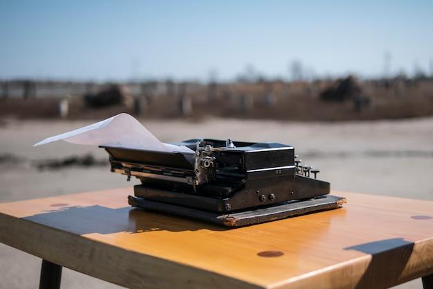 Schrijfmachine op de tafel in de open lucht, estuarium op de achtergrond