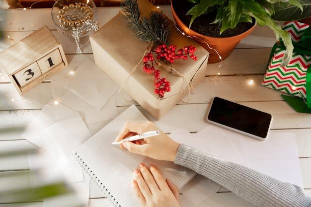 Schrijft wensen dromen van doelen plannen maak een lijst om in notitieboekje te schrijven vrouwelijke handen
