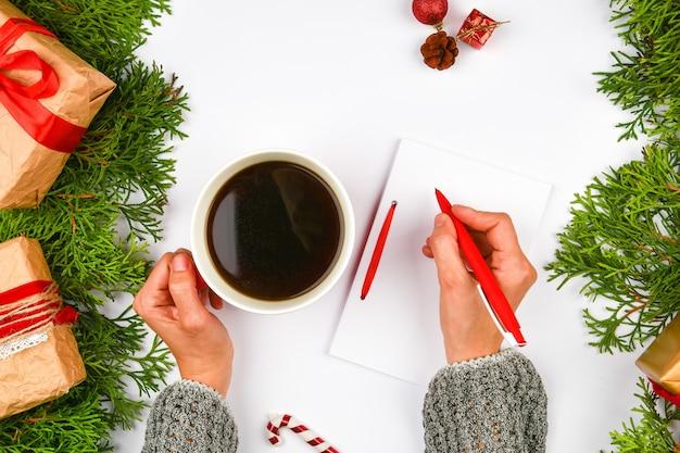 Schrijft wensen met een koffiemok