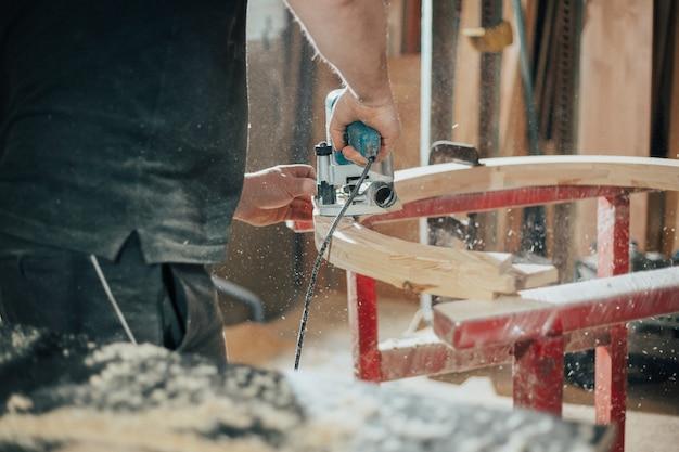 Schrijnwerkconcept, houtbewerking en meubelmakerij, professionele timmerman snijden hout in timmerwerkplaats, industrieel concept