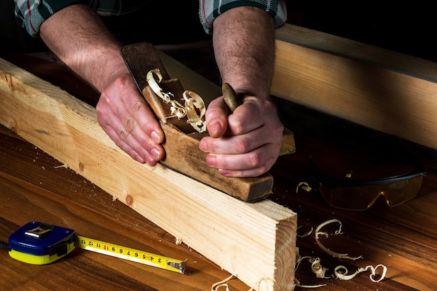 Schrijnwerker die een handvliegtuig gebruikt om een houten plank schoon te maken. handen van de hoofdclose-up op het werk.