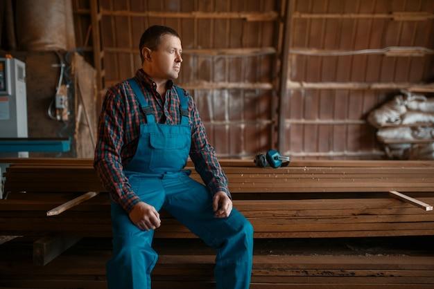 Schrijnwerker in uniform op zijn werkplek op houtfabriek, houtbewerkingsmachine, houtindustrie, timmerwerk. houtfabriek, boszagen in houtzagerij