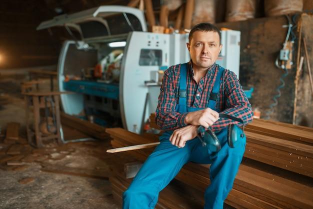 Schrijnwerker in uniform op zijn werkplek op houtfabriek, houtbewerkingsmachine, houtindustrie, timmerwerk. houtverwerking op fabriek, boszagen in houtzagerij