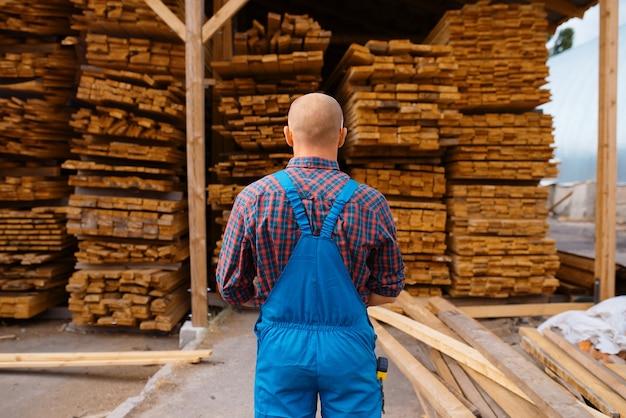 Schrijnwerker in uniforme checkboards op houtfabriek, houtindustrie, timmerwerk. houtverwerking op fabriek, boszagen in houtzagerij, magazijn buiten