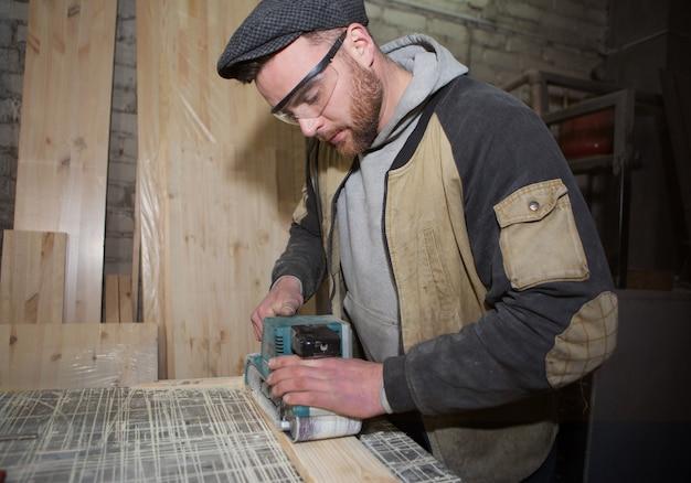 Schrijnwerker werkt met een handmatige elektrische schuurmachine op het bureaublad in productie