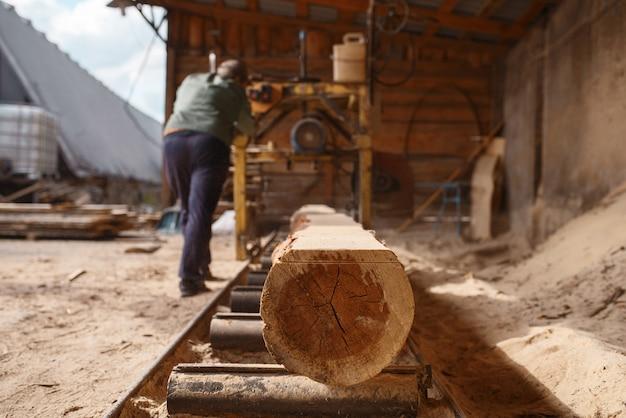 Schrijnwerker werkt op houtbewerkingsmachine, houtindustrie, timmerwerk. houtverwerking op fabriek, boszagen in houtzagerij, timmerwerk