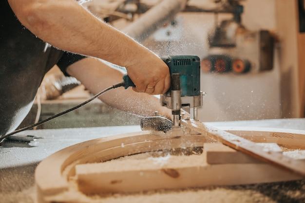 Schrijnwerkerij, houtbewerking en meubelmakerij, professionele timmerman die hout snijdt in timmerwerkplaats, industrieel concept