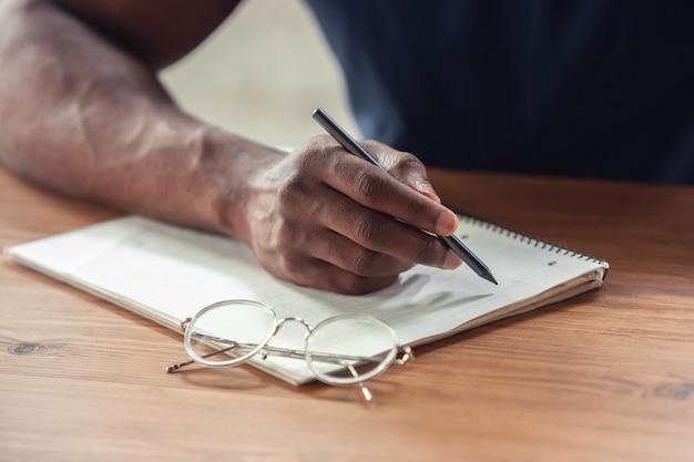 Schrijven. close up van afro-amerikaanse mannelijke handen, werkzaam in kantoor.