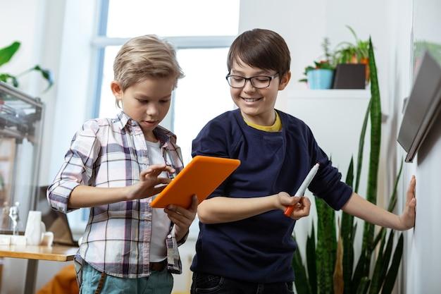 Schrijven op het bureau. stralend knappe jonge jongens met tablet en marker en schrijven op het duidelijke bureau writing