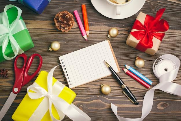 Schrijven van kerstkaarten open kladblok met pen op versierde houten tafel
