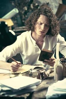 Schrijver aan het werk. jonge schrijver die aan de tafel zit en thuis iets schrijft in zijn schetsblok