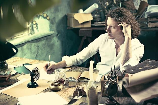Schrijver aan het werk. knappe jonge schrijver die aan de tafel zit en iets in zijn schetsblok schrijft