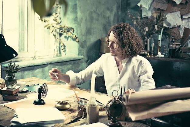 Schrijver aan het werk. knappe jonge schrijver die aan de tafel zit en thuis iets in zijn schetsblok schrijft