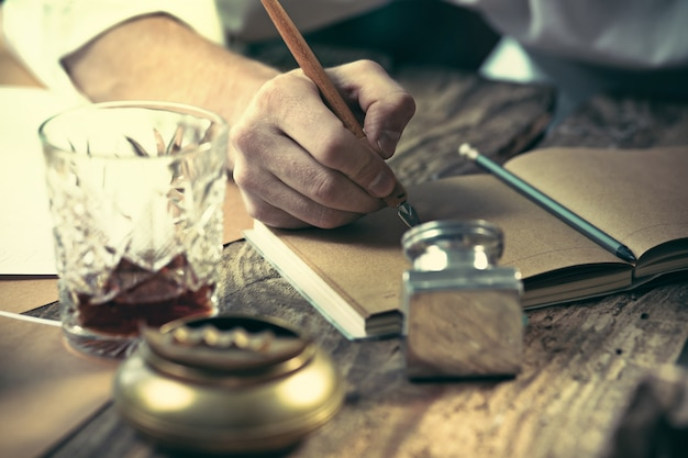 Schrijver op het werk. de handen van de jonge schrijver aan tafel zitten en iets in zijn schetsblok schrijven