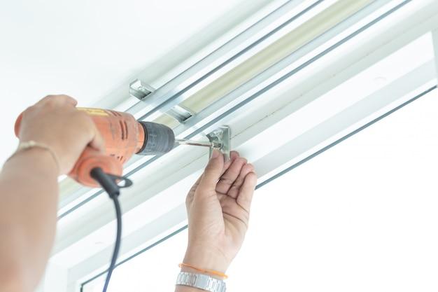 Schroef de schroeven om de gordijnen door professionele technici te installeren