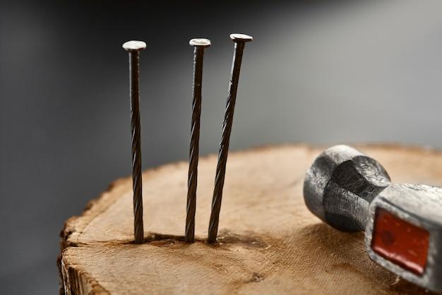 Schroef spijkers en hamer op de stronk. professioneel instrument, bouwmateriaal, bevestigingsmiddelen, bevestigings- en schroefgereedschap