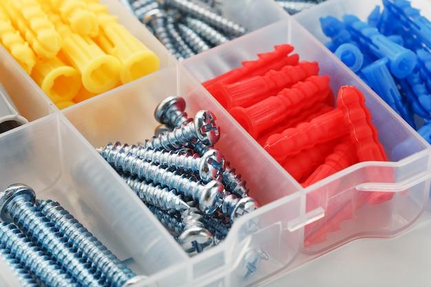 Schroeven en kunststof pluggen in verschillende maten, voor reparatie, constructie en installatie. detailopname