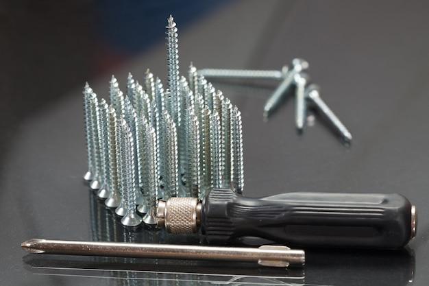 Schroeven met een schroevendraaier liggend op de tafel, schroef, schroevendraaier, gereedschapstoebehoren