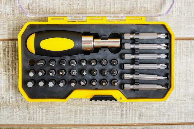 Schroevendraaier en sproeiers in een plastic doos, kopieerplaats, schroevendraaier sproeiers op houten oppervlak