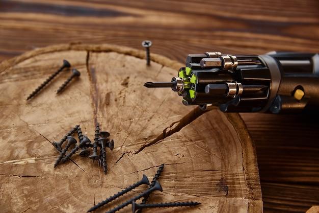 Schroevendraaier en zelftappende schroeven op boomstronk, close-up, houten tafel. professioneel instrument, timmermansuitrusting, houtbewerkingsgereedschap
