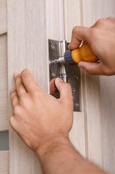 Schroevendraaier installeert schroef op roestvrijstalen deurscharnieren met houten draaideur