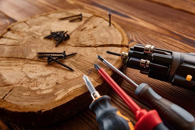 Schroevendraaiers en zelftappende schroeven op boomstronk, close-up, houten tafel. professioneel instrument, timmermansuitrusting, houtbewerkingsgereedschap