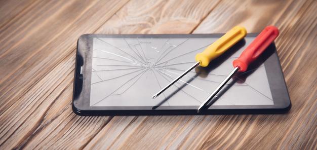 Schroevendraaiers op de gebroken tablet op de houten tafel