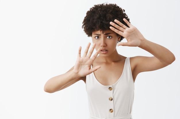 Schuchtere vrouw die slachtoffer wordt van huiselijk geweld, bang is voor klappen, gezicht bedekt, zichzelf beschermt met opgeheven handpalmen, bezorgd en nerveus kijkt, onzeker staat