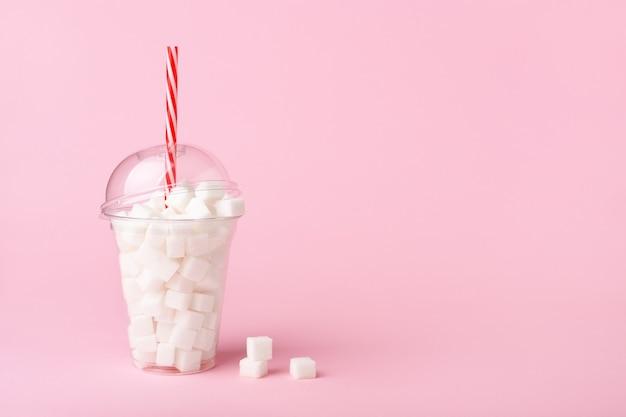 Schud glas met stro vol suiker op roze achtergrond. ongezonde voeding concept. kopieer ruimte, zijaanzicht.