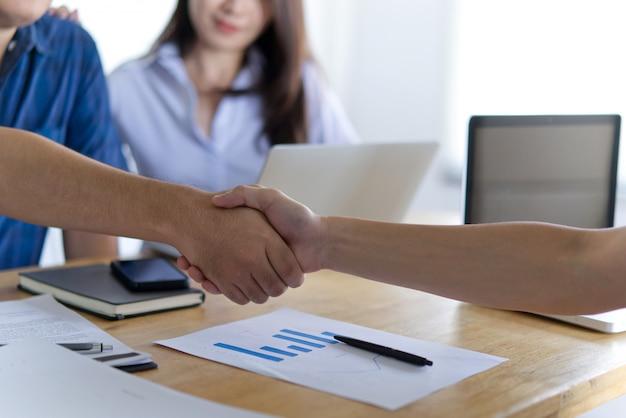 Schuddende handen tussen twee bedrijfsmannen en jonge vrouw die hen bekijken en glimlachen.
