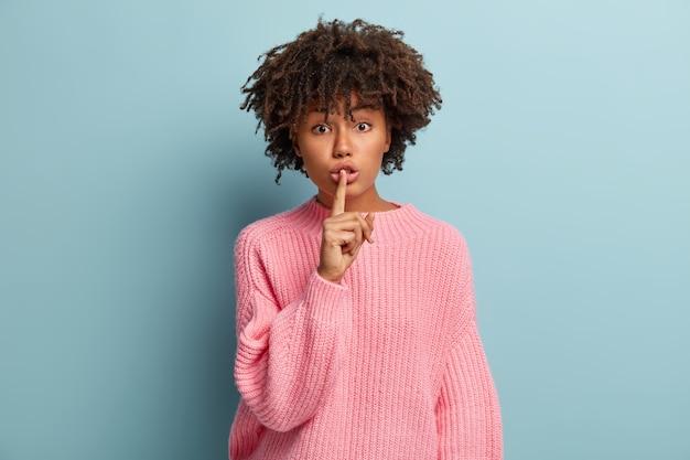 Schuif geen woord uit. bezorgde zwarte vrouw zwijgt, houdt de wijsvinger over de lippen, vraagt om geheim te bewaren, gekleed in losse roze trui, geïsoleerd over blauwe muur. wees stil en stom.