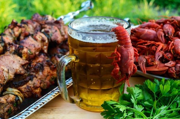 Schuimend bier in een glas en gekookte langoesten, gegrild vlees aan spiesjes. voor de vakantie, genieten van het buitenleven.