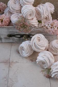 Schuimgebakjes in een houten doos en roze bloemen