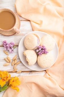 Schuimgebakjes taarten met kopje koffie op een witte houten oppervlak en oranje linnen textiel