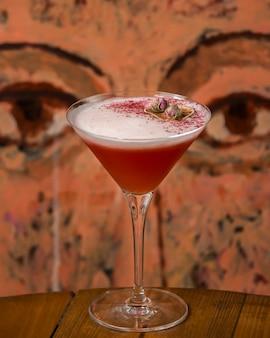 Schuimige rode cocktail gegarneerd met gedroogde rozenknoppen