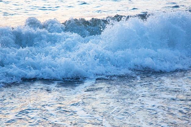 Schuimige witte golven op het zandstrand van de oostzee. blauwe zee en helderblauwe lucht, vloed. zomer op het strand