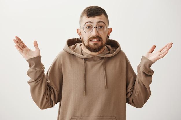 Schuldige, onhandige hipster met een bril met gespreide handen zonder idee en schouderophalend