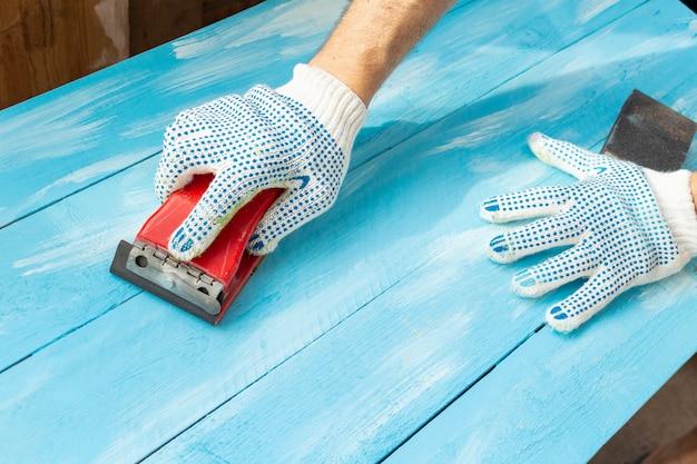 Schuren met schuurmiddelen in een hand houten geschilderde blauwe houten tafel