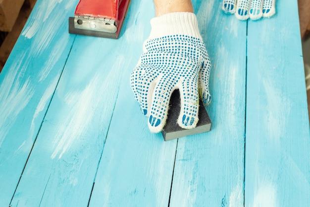 Schuren met schuurpapier spons in een hand houten blauw geschilderd