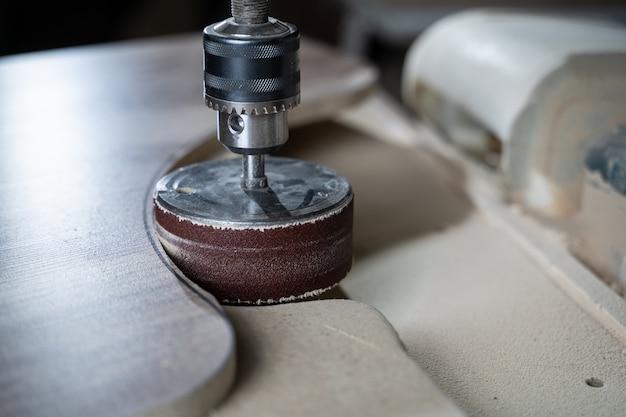 Schuurmachine, de timmerman gebruikt een polijstmachine om het hout glad te maken