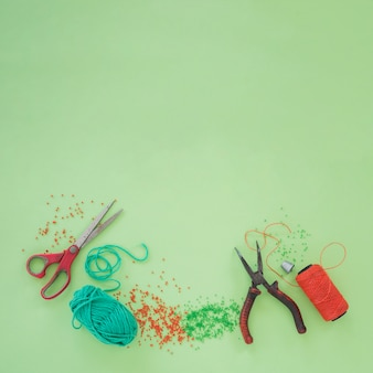 Scissor; tang; wol; kralen en een oranje garenspoel op groene achtergrond