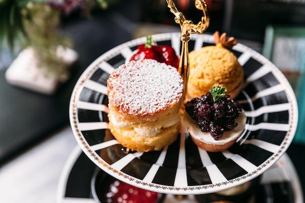 Scone pie-topping met suikerglazuur en blueberry mini tart op zwart-witte plaat.
