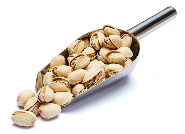 Scoop van geroosterde pistachenoten noten op witte tafel