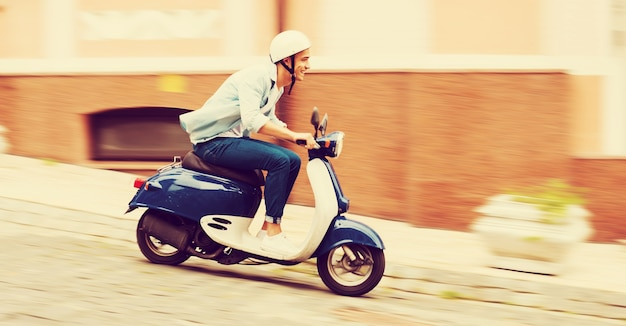 Scooterrit. zijaanzicht van jonge man in helm scooter rijden langs de straat en glimlachend