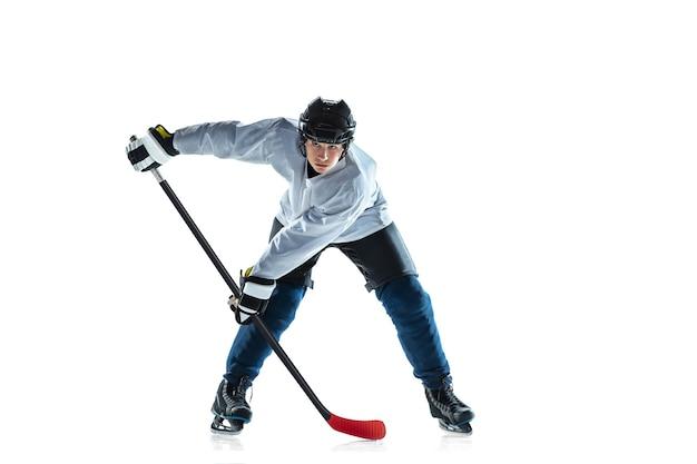 Scoren. jonge mannelijke hockeyspeler met de stok op ijsbaan en witte achtergrond. sportman met uitrusting en helm oefenen. concept van sport, gezonde levensstijl, beweging, beweging, actie.