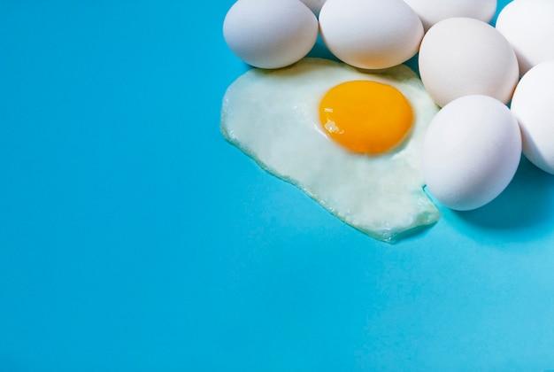 Scrambled op een blauw omringd door rauwe eieren.
