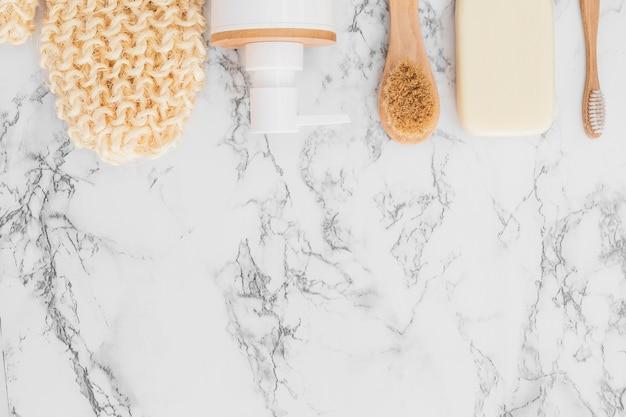 Scrub handschoen; cosmetische fles; zeep en penseel op marmeren achtergrond