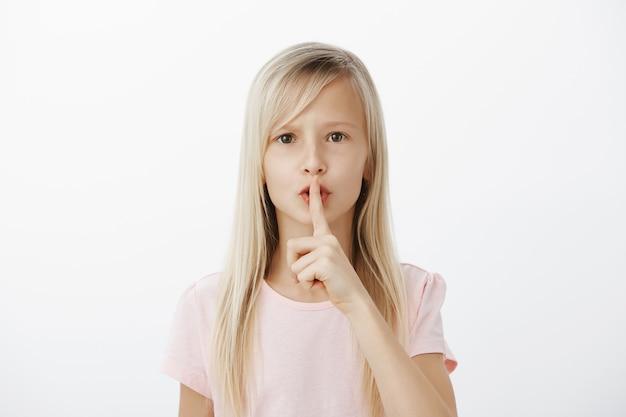 Sctrict zelfverzekerd klein blond meisje in casual roze t-shirt, zegt shh terwijl ze een stil gebaar toont met wijsvinger voor de mond, vraagt om stil te zijn terwijl ze voor babybroer zorgt