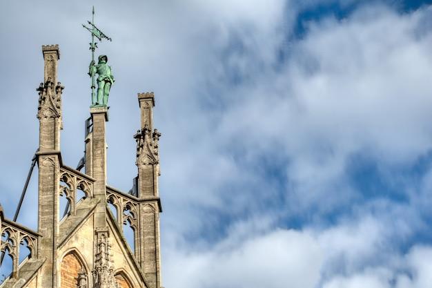 Sculptuur van krijger op de top van het oude huis van het nieuwe stadhuis op een achtergrond van blauwe bewolkte hemel in münchen, beieren, duitsland.