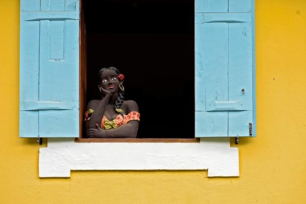 Sculptuur van vrouw buste op blauwe venster